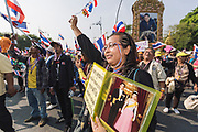 An Anti-Government protester carrying a portrait of the King and Queen of Thailand celebrating at a rally aimed at unseating the Prime Minister of Thailand. Anti-Government protesters led by the People's Democratic Reform Committee's (PDRC) marched towards Government House in Bangkok on Monday 9th December, 2013, where they heard the news that Prime Minister, Yingluck Shinawatra, brother of former Prime Minister Thaksin Shinawatra, had announced the dissolution of the Thai Parliament, leading to new elections.