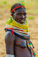 Pregnant Nyangatom tribe woman wearing a large number of beaded necklaces, Omo Valley, Ethiopia.