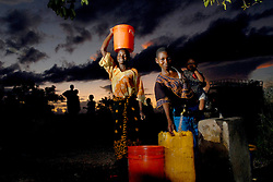 Somoe Mohamed, left, the mother of Hassan Dadi, who lost his arm after a lion ripped it off, gathers water at sunset in the village of Usuru, Tanzania. Sunrise and sunset are very dangerous times for the women to be outside because of the lion attacks. Ami Vitale