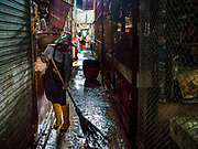 29 JUNE 2017 - SAMRONG NUEA, SAMUT PRAKAN, THAILAND: A laborer cleans an aisle in the market in Samrong Nuea district, Samut Prakan province.      PHOTO BY JACK KURTZ