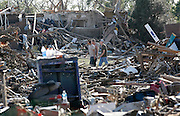 People walk through their tornado-ravaged neighborhood  in Moore, Oklahoma May 21, 2013. A massive tornado tore through a suburb of Oklahoma City, wiping out whole blocks and killing at least 24.   REUTERS/Rick Wilking (UNITED STATES)