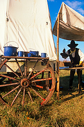 man cooking under a tent on the back of a wagon