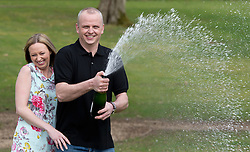 Neil Trotter a  car mechanic and racing driver from Coulsdon, United Kingdom celebrates with  his partner Nicky Ottaway at a hotel in Dorking, United Kingdom, after winning  £108 million (pounds sterling) in the EuroMilllions lottery, Tuesday, 18th March 2014. Picture by David Dyson / i-Images