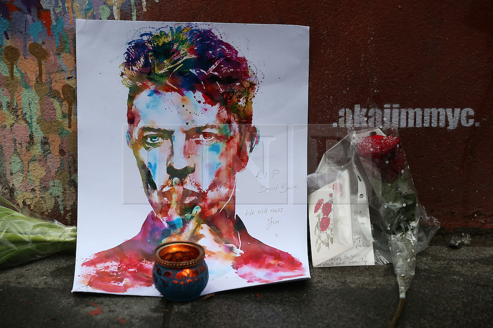 © Licensed to London News Pictures. 11/01/2016. London, UK. Tributes are placed at a mural of David Bowie in Brixton. The Death of David Bowie, who was born in Brixton, has been announced today.  Photo credit: Peter Macdiarmid/LNP