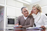 Middle-aged couple sitting in kitchen counting bills using calculator