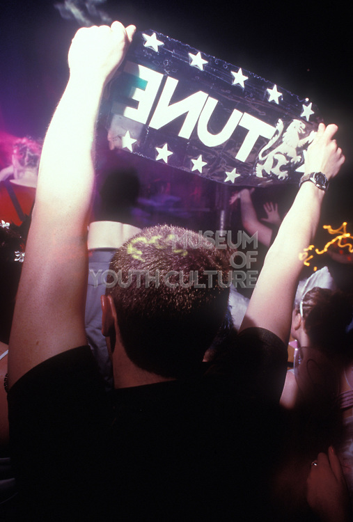 A man holding up a 'Tune' sign, Clubbing, UK 1997
