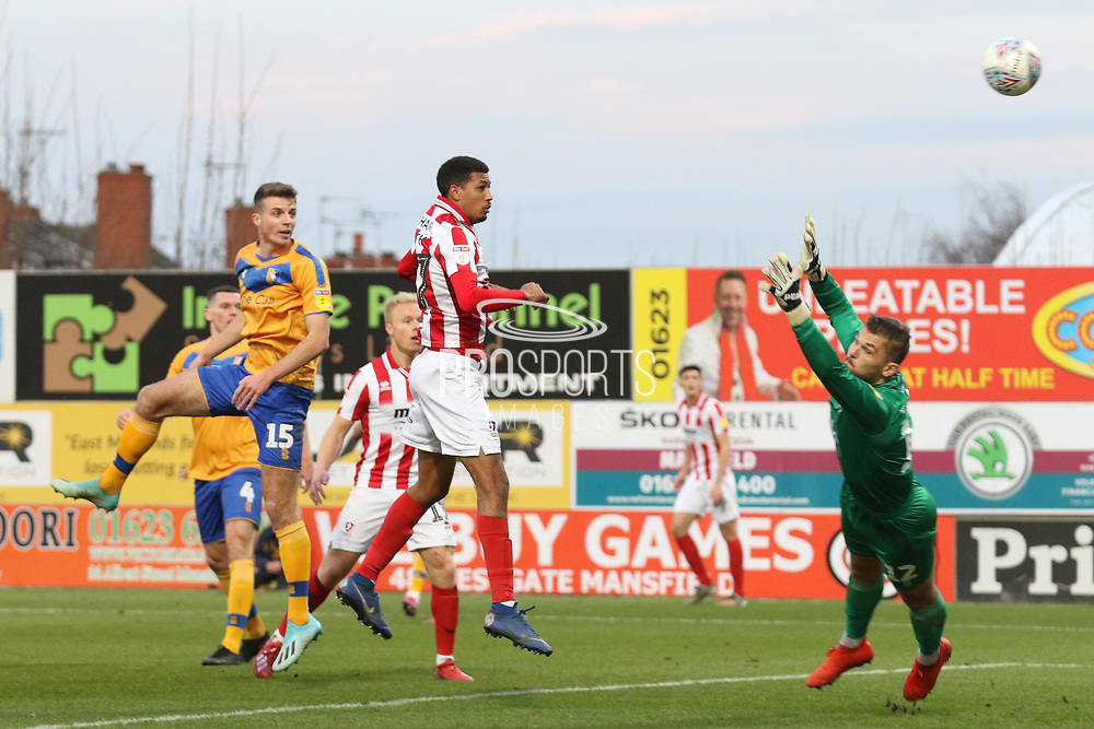 Jonte Smith heads the ball over Bobby Olejnik to score  during the EFL Sky Bet League 2 match between Mansfield Town and Cheltenham Town at the One Call Stadium, Mansfield, England on 7 December 2019.