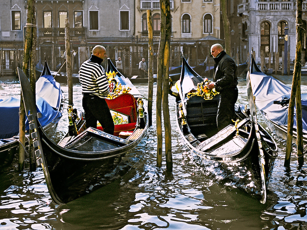 Two gondolieri converse standing in their gondolas as they prepare them for the day.  Gondolas are ornamented with small gilded statues as well as the polished prow ferri.