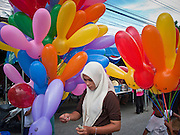 "Sept 29, 2009 - YARANG, THAILAND: A Muslim woman walks among balloons for sales at a street fair in Yarang, Thailand, Sept. 29. Thailand's three southern most provinces; Yala, Pattani and Narathiwat are often called ""restive"" and a decades long Muslim insurgency has gained traction recently. Nearly 4,000 people have been killed since 2004. The three southern provinces are under emergency control and there are more than 60,000 Thai military, police and paramilitary militia forces trying to keep the peace battling insurgents who favor car bombs and assassination.   Photo by Jack Kurtz / ZUMA  Press"