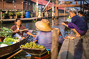 17 JANUARY 2013 - DAMNOEN SADUAK, RATCHABURI, THAILAND: A vegetable vendor does business with local residents before tourists arrive at the Damnoen Saduak (also spelled Damnoensaduak) floating market. The floating market in Damnoen Saduak is one of the best known tourist attractions in Thailand. The canal was dug in the 1860's to connect to provincial towns south of Bangkok. At the time it was the straightest, longest canal in Thailand. Thousands of tourists, both foreign and Thai, visit Damnoen Saduak to see the floating market and experience canal life.     PHOTO BY JACK KURTZ