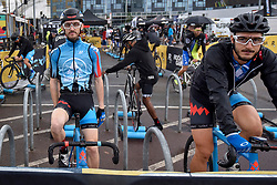 © Licensed to London News Pictures. 22/07/2017. London, UK. World class international cyclists warm up on stationary bikes ahead of the London stage of the Red Hook Criterium around Greenwich Peninsula.  Heavy rain showers made riding laps around the 1km street circuit on fixed gear bicycles with no brakes even more of a challenge as riders negotiated multiple heats to try to qualify for an evening final. Photo credit : Stephen Chung/LNP