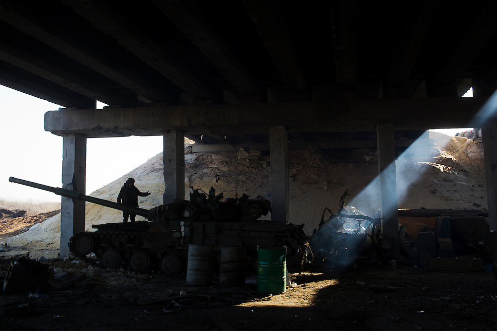 A member of Dnipro-1 battalion is seen atop a tank under a fortified bridge about two kilometers from the front on March 9, 2015 near Pisky, Ukraine.