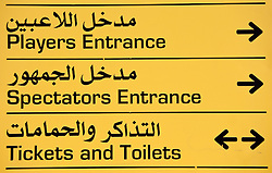 Signs in Arabic and English at the Qatar Sports Club Stadium to the Players Entrance, Spectators Entrance and Tickets and Toilets