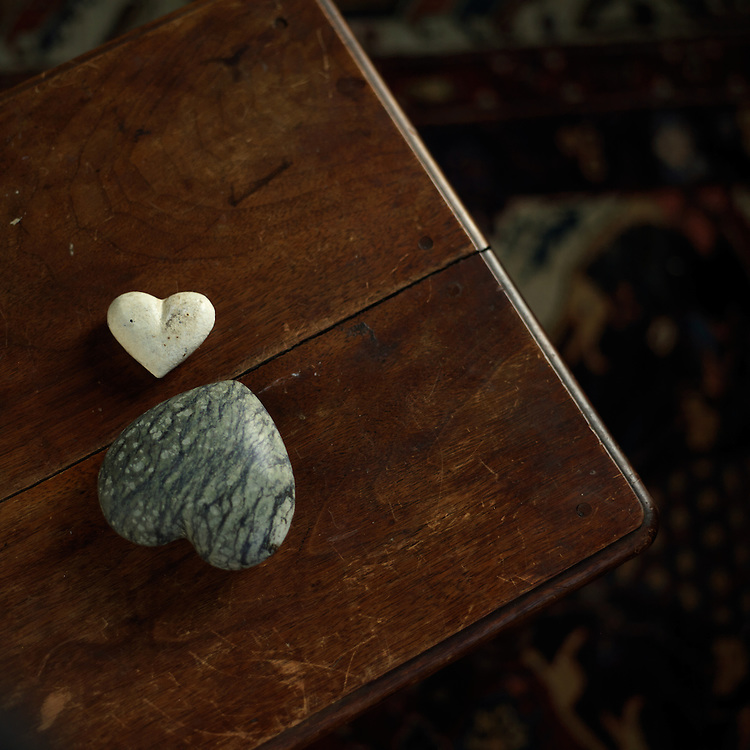 Two heart-shaped rocks on a wood table