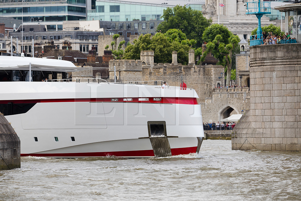 """© Licensed to London News Pictures. 16/06/2018. London, UK.  Bruce Grossman's 180 feet long superyacht, Forever One sails on the River Thames in London passing under Tower Bridge. Bruce Grossman is one of the richest men in Mexico (estimated net worth of USD1.5 billion) and shareholder of Arca Continental, the second largest Coca-Cola bottler in Latin America and third largest in the world. The unusual red colour scheme of the yacht reflects Grossman's significant Coca-Cola business interests and the yacht also features a reverse bow, fold-down balconies and a beach club with large window in the transom. The name Forever One refers to Bruce's wife Elsa, the childhood best friend of his younger sister and who later became Grossman's """"forever one""""..  Photo credit: Vickie Flores/LNP"""
