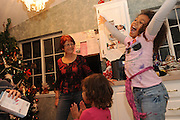 SUN-STAR PHOTO BY BEA AHBECK<br /> Jasmine is very happy over getting a WII on Christmas eve Dec. 24, 2010. Her grandmother Renate watches, and Dessira claps her hands.