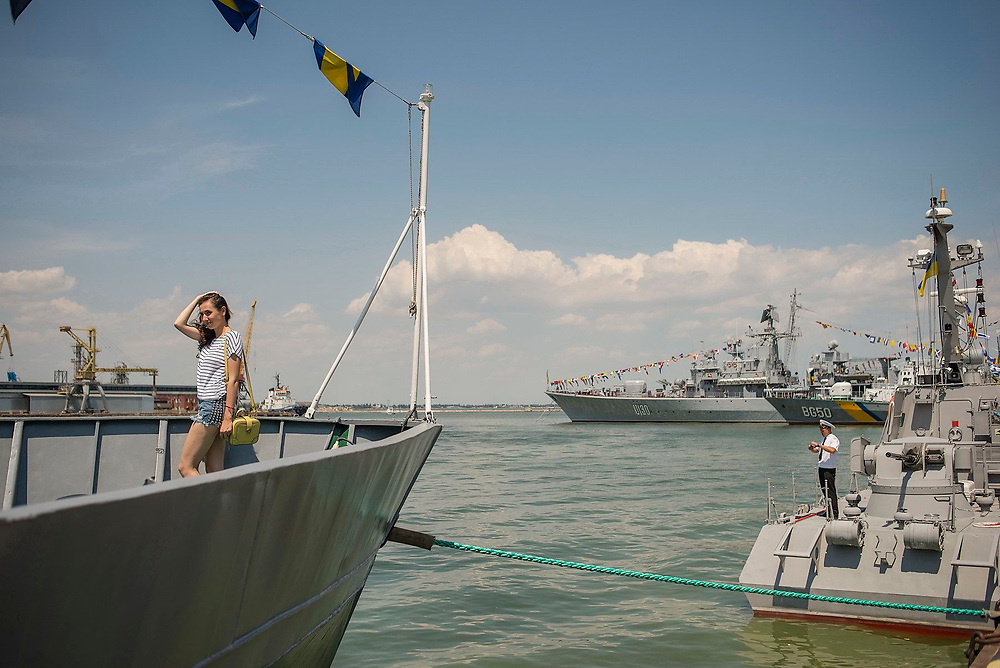 A girl arrange his hair as she is being photograph by a friend. Navy war ships are opened to public for Navy Day, held in Odessa for the second time since Russia's seizure of Crimea in 2014.