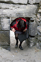 Tourist exploring the interior of Teampall Chaomhan a 10-14th century church ruins on Inis Oirr the Aran Islands Galway Ireland
