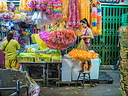 24 FEBRUARY 2016 - BANGKOK, THAILAND: A woman hangs plastic streamers in her stall in Pak Khlong Talat. Bangkok government officials announced this week that vendors in Pak Khlong Talat, Bangkok's well known flower market, don't have to move out on February 28. City officials are trying to clear Bangkok's congested sidewalks and they've cracked down on sidewalk vendors. Several popular sidewalk markets have been closed in recent months and the sidewalk vendors at the flower market had been told they would be evicted at the end of the month but after meeting with vendors and other stake holders city officials relented and said vendors could remain but under stricter guidelines regarding sales hours. The flower market is one of the best known markets in Bangkok and has become a popular tourist destination.        PHOTO BY JACK KURTZ
