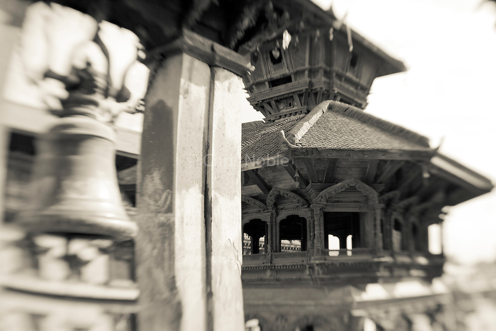 A bell and wooden temple in Bhaktapur's Durbar Square.