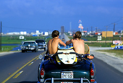 Stock photo of two teenage boys riding in the back seat of a convertible with surfboards