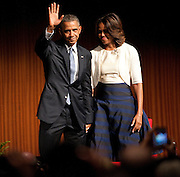 US President Barack Obama and First Lady Michelle Obama wave to the audience after speaking in the LBJ Library at the Civil Rights Summit on the campus of the University of Texas on 10 April 2014.