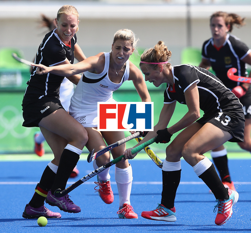 RIO DE JANEIRO, BRAZIL - AUGUST 19:  Gemma Flynn (C) of New Zealand is tackled by Katharina Otte (R) and Hannah Kruger during the Bronze medal match between Germany and New Zealand on Day 14 of the Rio 2016 Olympic Games held at the Olympic Hockey Centre on August 19, 2016 in Rio de Janeiro, Brazil.  (Photo by David Rogers/Getty Images)