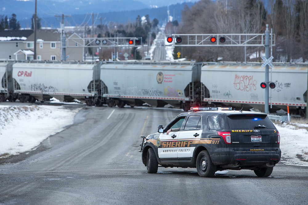 GABE GREEN/Press<br /> <br /> A Kootenai County Sheriff deputy sits parked at the intersection of Prairie Avenue and Idaho Street in  Post Falls Wednesday after a SUV had its bumper knocked off by a passing train.