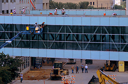 Stock photo of men elevated by machinery working on the sky bridge connecting the George R. Brown Convention Center to the Hilton Hotel in downtown Houston Texas