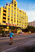 A roller skater passes art deco building the Cavalier on South Beach in Miami, FL.