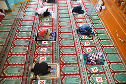 © Licensed to London News Pictures. 20/07/2020. London, UK. Muslim worshippers perform first prayer keeping two meters apart at Wightman Road Mosque, also known as London Islamic Cultural Society and Mosque, in north London as the Mosque reopens for Zuhr (the afternoon prayer) after almost four months of lockdown. Last month the government announced that gatherings of more than 30 worshippers are allowed for acts of communal worship in churches, synagogues, mosques, temples and other places of worship. All worshippers attending Mosques have to wear face coverings and bring their own prayer mat, Quran, and a reusable shoe bag. Photo credit: Dinendra Haria/LNP