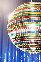Multi-coloured disco ball in front of blue stage curtain cropped