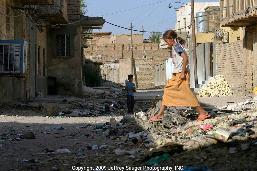 Children play in a pile of garbage in the modernized center of the village Suq ash Shuyukh on the outskirts of Nasiriyah, Iraq, Sunday, August 3, 2003.  ..Since the 1991 uprising against Saddam Hussein in Shiite dominated Southern Iraq, people of this area have suffered greatly through his methods of disrupting daily life. For example, modernization came to a hault as money was diverted to Baath Party strongholds. Check points on on every other corner made it nearly impossible to go to work, the doctor, or visit family. Teachers made $5 U.S. per month and had to spend almost all of their salary for taxis in order to go to work...He tried to kill the people by cutting off the rivers that village survival depends on. Dams and canals dirverted the fresh water from flowing into the swamps by way of tributaries. In effect, without fresh water flowing in, the people started poisoning the water supply themselves by using it to wash and clean. Their primitive sewers still flow freely into the same waters that animals use and that feed their rice fields.