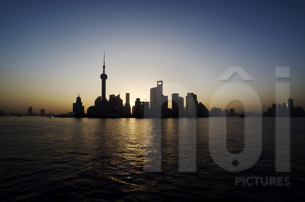 Shanghai's skyline at dawn with The Oriental Pearl TV Tower landmark in shadow puppet. China, Asia. Cityscape viewed from Huangpu river. China, Asia.
