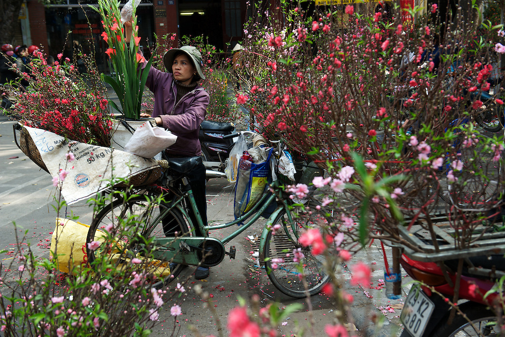 A flower seller plies her trade in the Old Quarter of Hanoi.