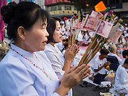 23 NOVEMBER 2014 - BANGKOK, THAILAND:  Women pray with monetary donations at a mass alms giving ceremony in Bangkok Sunday. 10,000 Buddhist monks participated in the ceremony on Rajadamri Road in front of Central World shopping mall. The alms giving was to assist Buddhist temples in the insurgency wracked southern provinces of Thailand, where Buddhist monks on their alms rounds have been targeted by Muslim extremists. The ceremony was sponsored by Wat Phra Dhammakaya, the center of the Dhammakaya Movement, a Buddhist sect founded in the 1970s. The temple has become active in Thai politics.    PHOTO BY JACK KURTZ