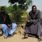 Dr Mohamed Bailor Barrie, co-founder of the Wellbody Alliance, with Kanye witch doctor, Alusine Kamara, near Koidu in the Kono district of eastern Sierra Leone. Kamara says he has the power to communicate with demons, and negotiates with them or enlists the help of demon allies to address cases of demonic possession or other forms of spiritual warfare. Barrie and his partner Dr Dan Kelly are trying to build a bridge between the witch doctor and the clinic to enable the witch doctor's patients to receive treatment in cases that Barrie feels are beyond the witch doctor's abilities. There is deep distrust on both sides.