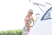 Female friends loading luggage in car trunk against clear sky