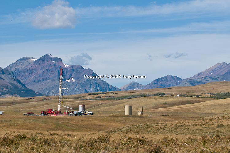 drill rigs set up to drill natural gas and oil on the blackfeet reservation with rising wolf mountain glacier national park, montana, usa in the background