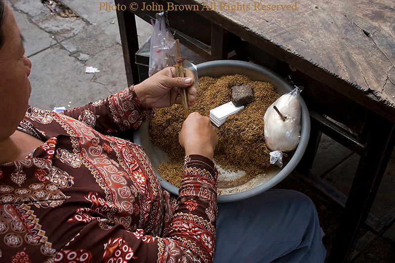 A woman is rolling hand made cigarettes on a sidewalk in Phnom Penh, Cambodia.
