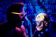 Man with glowing glasses holding a glowing skull.Black light