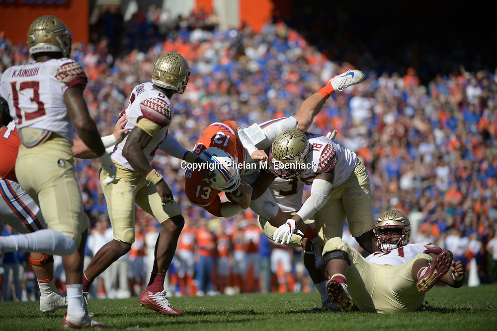 Florida quarterback Feleipe Franks (13) is upended by Florida State linebacker Matthew Thomas (6), defensive back Derwin James (3) and linebacker Ro'Derrick Hoskins (18) on a quarterback keeper during the first half of an NCAA college football game Saturday, Nov. 25, 2017, in Gainesville, Fla. (Photo by Phelan M. Ebenhack)