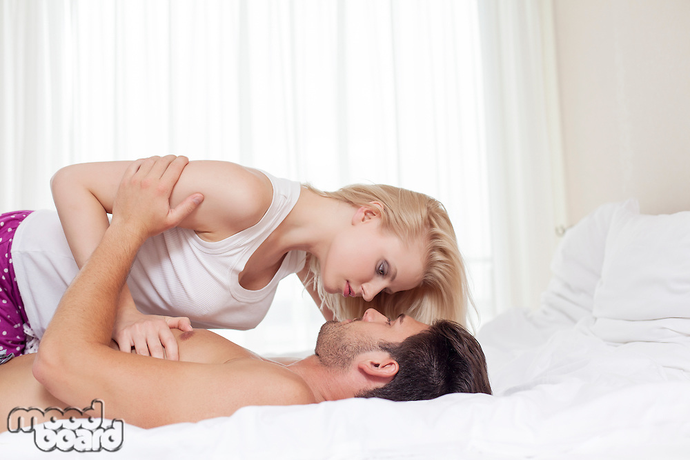 Side view of young couple cuddling in bed