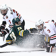Mike McMurtry #7 of the Northeastern Huskies, Connor Brickley #23 of the Vermont Catamounts, and Josh Manson #3 of the Northeastern Huskies fight for the puck in front of the net during the game at Matthews Arena on January 18, 2014 in Boston, Massachusetts. (Photo by Elan Kawesch)