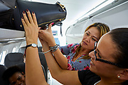 A Silver Airways flight attendant helps a passenger safely stow her carry-on luggage.