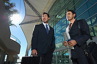 Two businessmen standing outside office building, low angle view