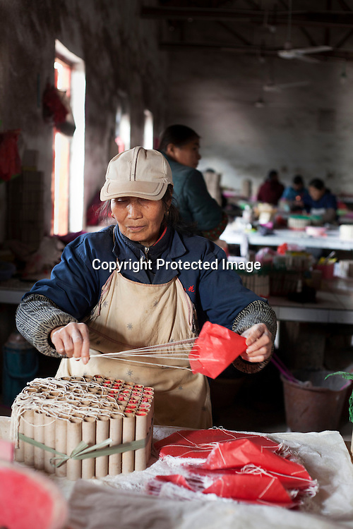 Hunan, Liuyang, Dec. 19..2013 : Xiao Shulan, a worker, assembles  fireckrackers for the Western market in a factory .