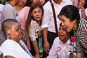 27 FEBRUARY 2013 - BANGKOK, THAILAND: Pol Gen PONGSAPAT PONGCHAREON (center) and YINGLUCK SHINAWATRA, Prime Minister of Thailand, (right) talk to a woman severely burned while they campaign for Pongsapat's election to Governor of Bangkok. Police General Pongsapat Pongcharoen (retired), a former deputy national police chief who also served as secretary-general of the Narcotics Control Board is the Pheu Thai Party candidate in the upcoming Bangkok governor's election. (He resigned from the police force to run for Governor.) Former Prime Minister Thaksin Shinawatra reportedly personally recruited Pongsapat. Most of Thailand's reputable polls have reported that Pongsapat is leading in the race and likely to defeat Sukhumbhand Paribatra, the Thai Democrats' candidate and incumbent. The loss of Bangkok would be a serious blow to the Democrats, whose base is the Bangkok area.     PHOTO BY JACK KURTZ