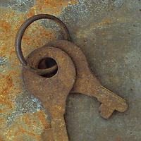 Two small simple rusty keys on keyring lying on rusty metal sheet