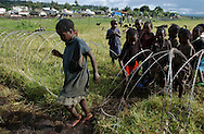 Kiwanja, Congo  Children displaced by fighting in Eastern Congo cross the barbed wire fence that separates their camp from a U.N. compound next door. U.N. peacekeepers have been criticized for failing to protect civilians during recent months of fighting. (Photo by Miguel Juárez Lugo).